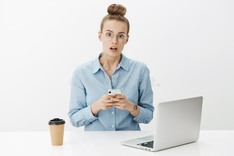 Portrait of shocked and confused woman receiving concerning and troublesome message via smartphone open mouth and widen. Eyes at camera from amazement sitting royalty free stock photos