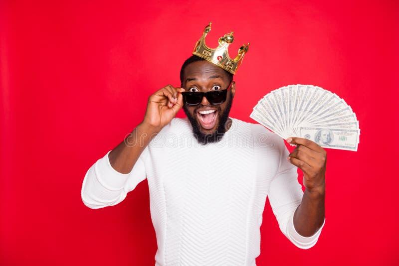 Portrait of shocked crazy dark skin man brown hair bearded hold fan of money scream wow win cashback x-mas lottery in. Portrait of shocked crazy dark skin man stock photography