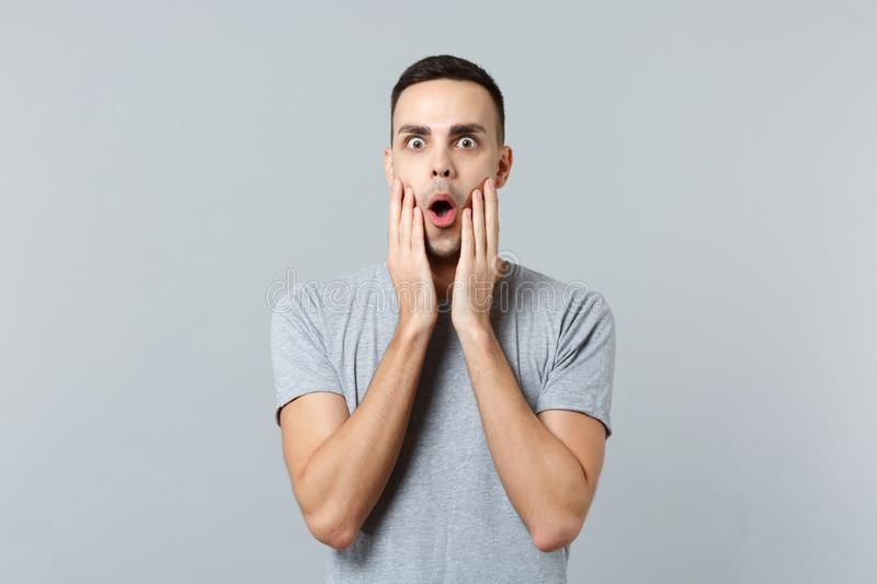 Portrait of shocked excited young man in casual clothes keeping mouth open, putting hands on face isolated on grey stock images
