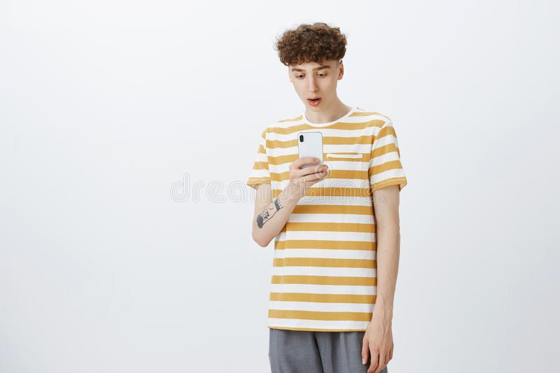 Portrait of shocked guy being surprised cool chick swiped him in date app dropping jaw staring impressed at smartphone. Screen as standing speechless over gray stock image