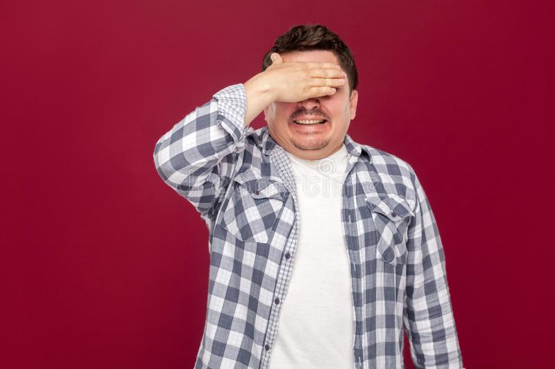 Portrait of shocked handsome middle aged business man in casual checkered shirt standing, closed his eyes with hand and do not royalty free stock images