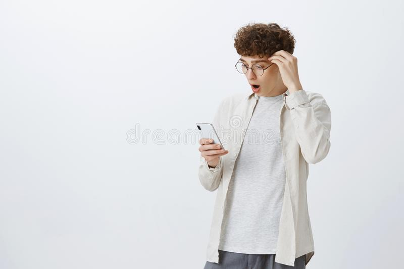 Portrait of shocked and impressed good-looking stylish man with curly hairstyle in round glasses dropping jaw as reading stock photo
