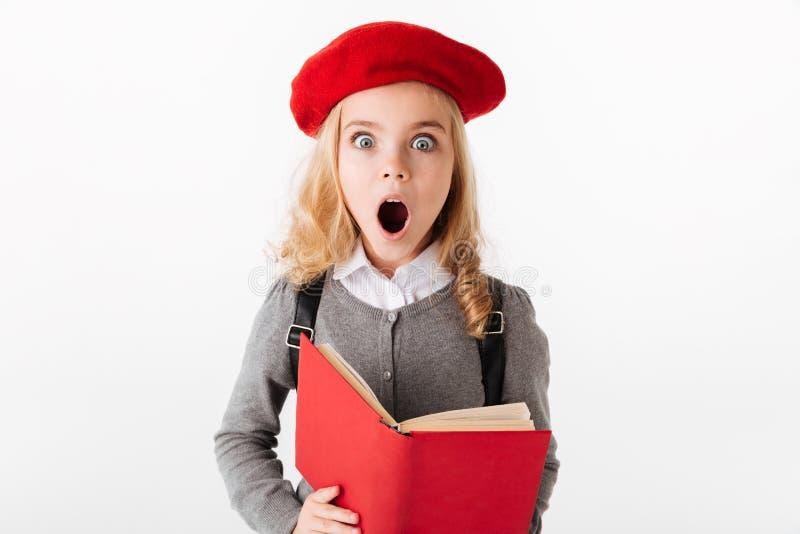 Portrait of a shocked little schoolgirl dressed in uniform royalty free stock photo