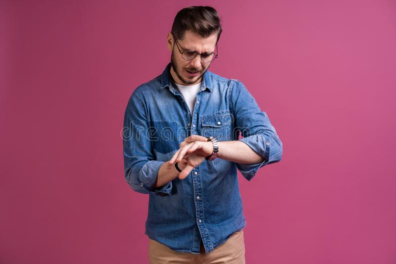 Portrait of a shocked man looking on wrist watch over pink background. Portrait of a shocked man looking on wrist watch over pink background royalty free stock photography