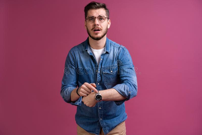Portrait of a shocked man looking on wrist watch over pink background. Portrait of a shocked man looking on wrist watch over pink background stock image