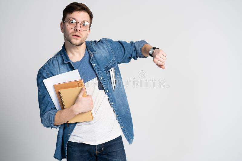 Portrait of a shocked man looking on wrist watch over white background. Portrait of a shocked man looking on wrist watch over white background royalty free stock photography