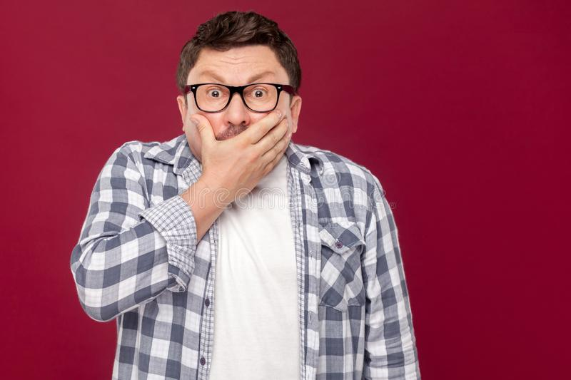 Portrait of shocked middle aged business man in casual checkered shirt and eyeglasses standing, covering his mouth and looking at stock image