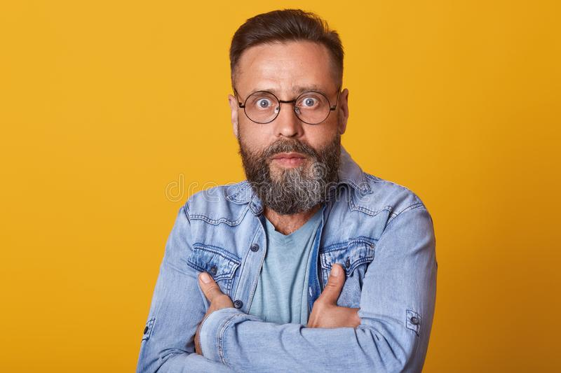 Portrait of shocked middle aged man in full disbelief. Hipster male with beard wears denim jacket posing isolated over yelow stock photo
