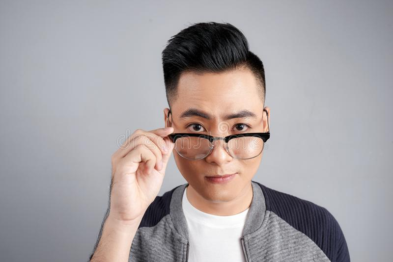 Portrait of shocked modern man touching his spectacles stock image