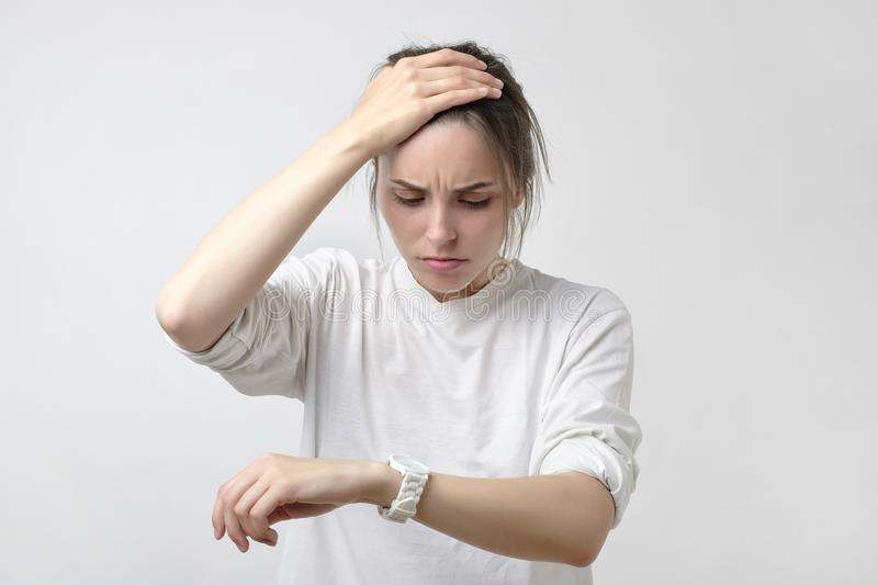 Portrait of shocked sad young woman holding hand with wrist watch. stock photo