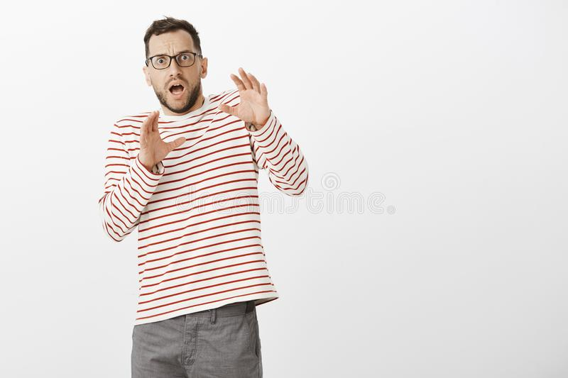 Portrait of shocked terrified adult european father in glasses and striped pullover, bending backwards with raised hands stock photography