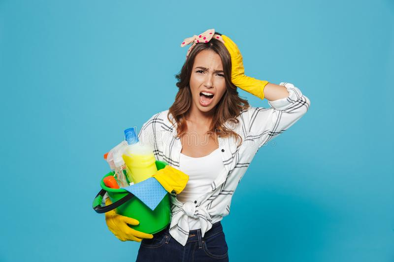 Portrait of shocked upset housemaid 20s wearing yellow rubber gloves for hands protection holding bucket with cleaning stock image