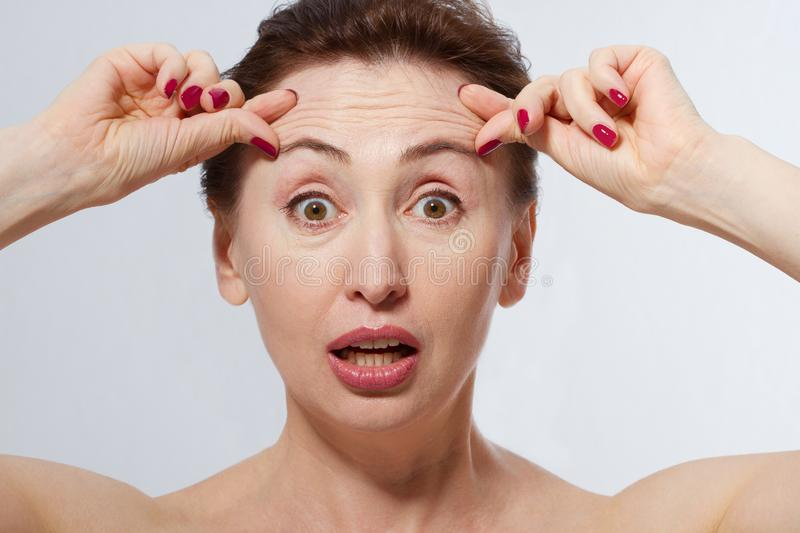 Portrait of Shocked Woman with wrinkles on the forehead. Collagen and face injections concept. Menopause. Cropped image. Copy spac royalty free stock images