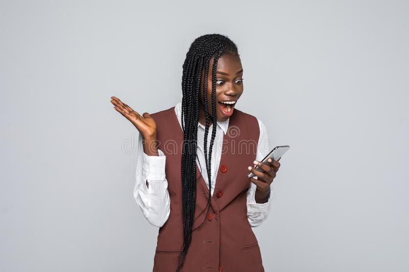 Portrait of shocked young african woman holding mobile phone over gray background stock image