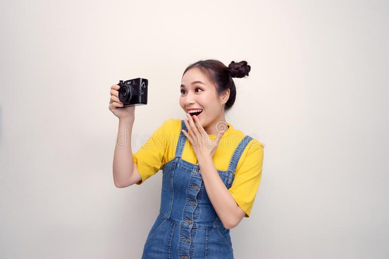 Portrait of a shocked young girl dressed in denim jumpsuit holding photo camera isolated over white background stock images