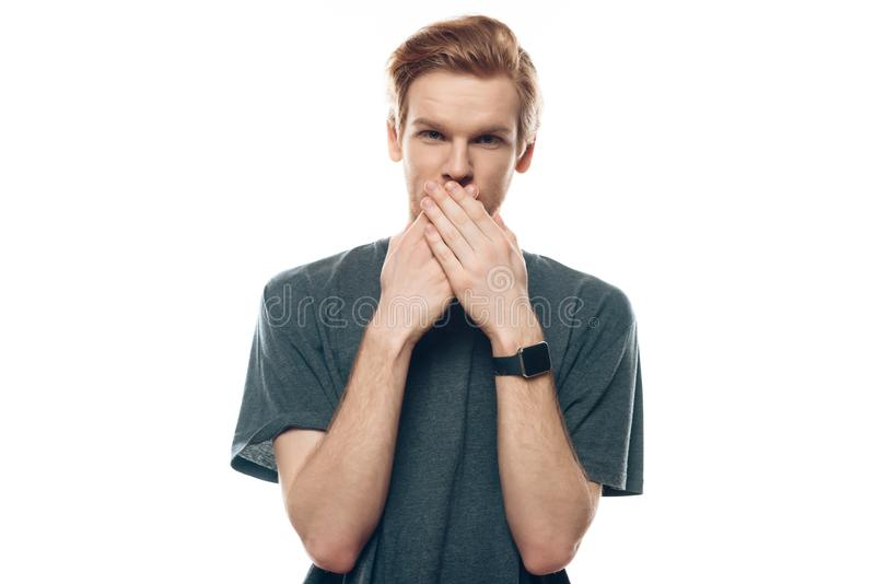 Portrait Shocked young man covers mouth with hands royalty free stock images