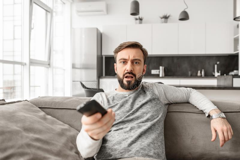 Portrait of a shocked young man holding TV remote control royalty free stock images