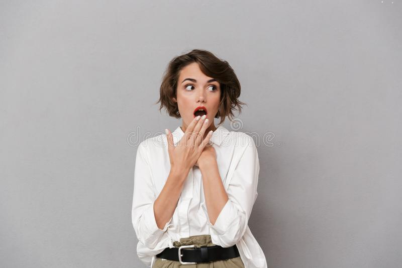 Portrait of a shocked young woman dressed in white shirt stock images
