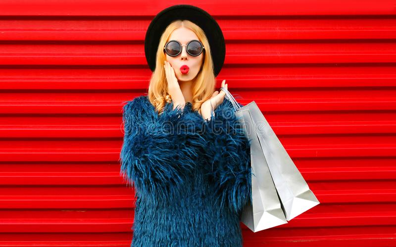 Portrait shocked young woman with shopping bags wearing blue faux fur coat, black round hat and sunglasses posing over red wall stock images