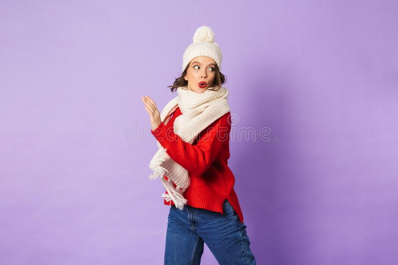 Shocked young woman wearing winter hat isolated over purple background. Portrait of a shocked young woman wearing winter hat isolated over purple background royalty free stock photos