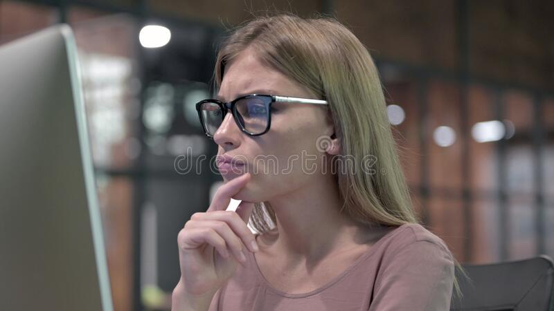 Portrait Shoot of Thoughtful Woman working on Computer stock image