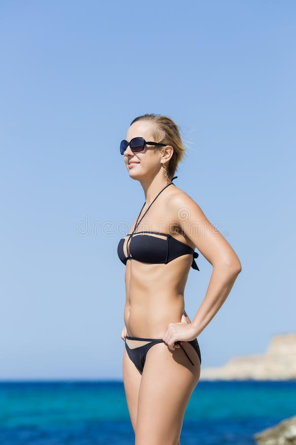 Portrait of short-haired smiling blond woman against sea stock images