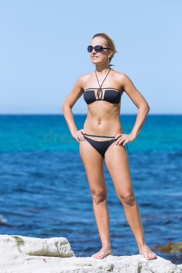 Portrait of short-haired smiling blond woman against sea stock photos