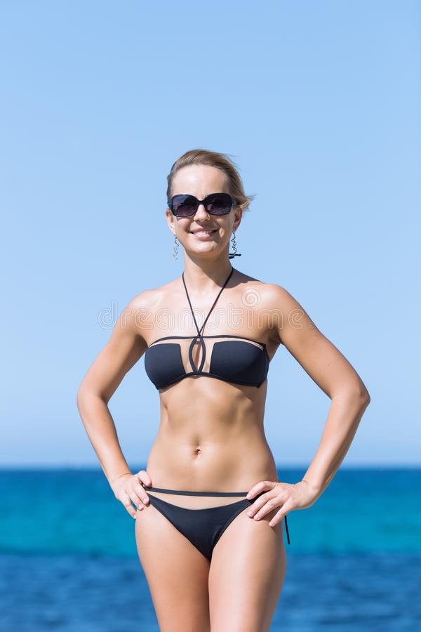 Portrait of short-haired smiling blond woman in black swimsuit stock photo