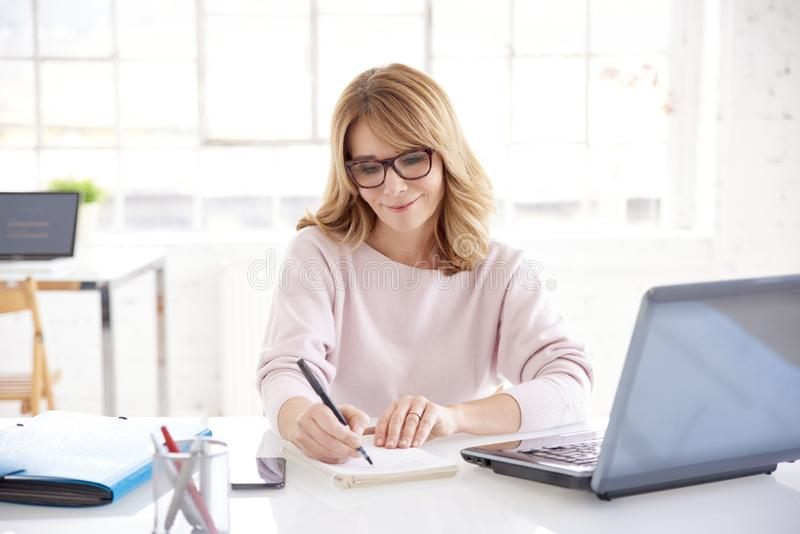 Middle aged businesswoman sitting at office desk and working on business plan stock photography