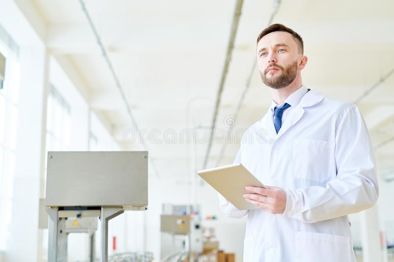 Operating Machine at Packaging Department. Portrait shot of confident bearded worker wearing white coat using digital tablet while operating machine at packaging stock photo