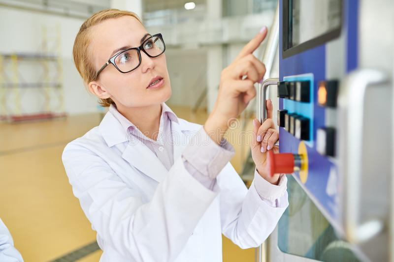 Operating CNC Machine. Portrait shot of confident pretty factory worker wearing eyeglasses and white coat operating CNC machine at spacious production department stock image