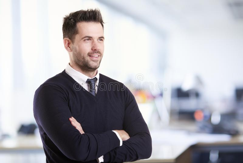 Businessman standing with folded arms in the office royalty free stock images