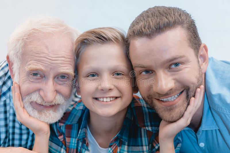 Portrait shot of little boy, grandfather and father smiling and looking stock photography