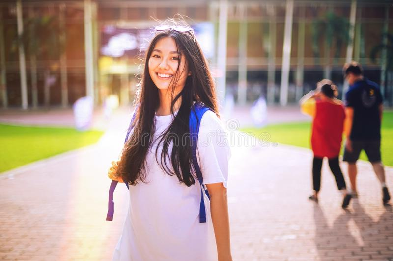 Portrait shot of young Asian female student smiling outdoor. Portrait shot of pretty young Asian female university student smiling outdoor with light leaks from stock image