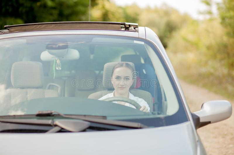 Portrait shot through windshield of pretty woman in car stock image