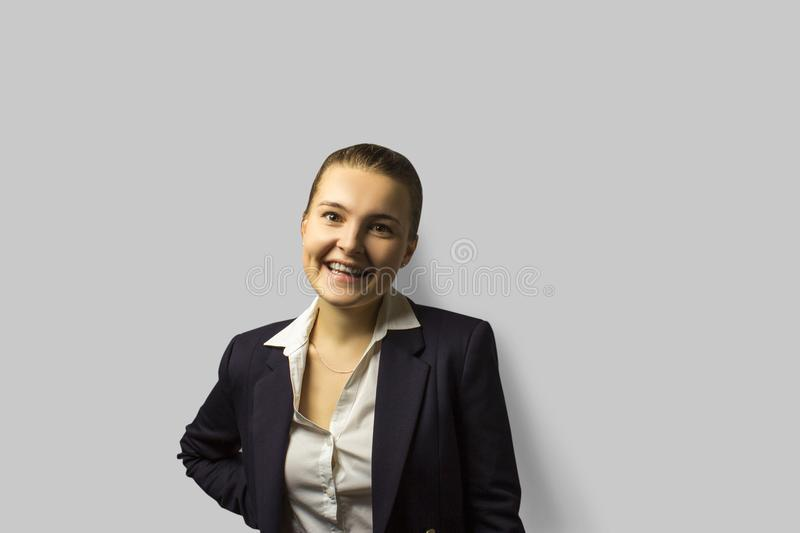 Portrait shot. young beautiful business woman with short hair combed back, wearing a jacket. widely smiling. stock photo