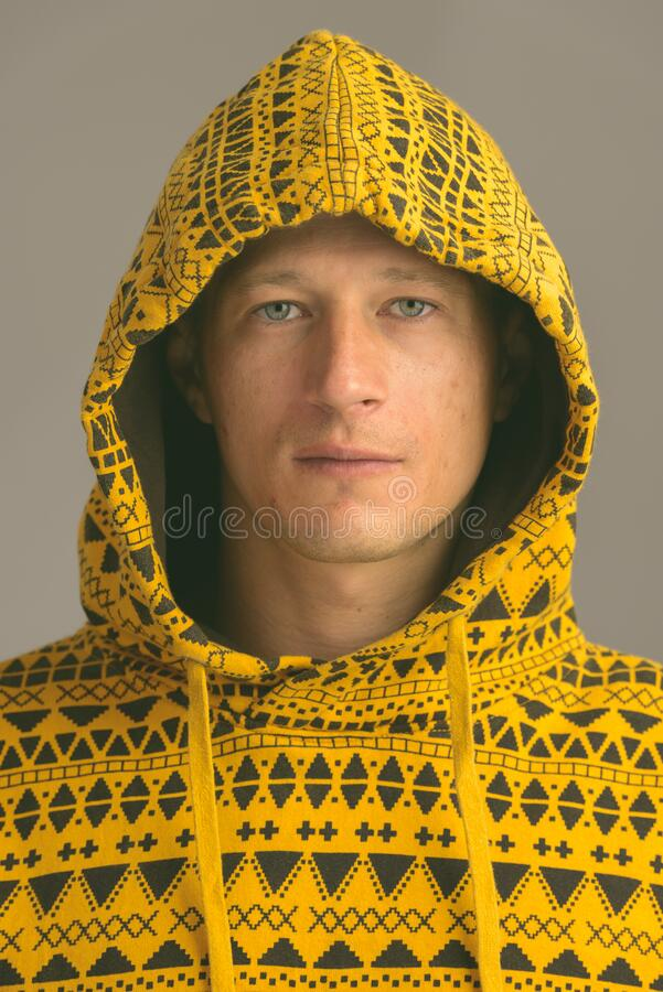 Portrait shot of young handsome Caucasian man isolated against gray gradient background royalty free stock images