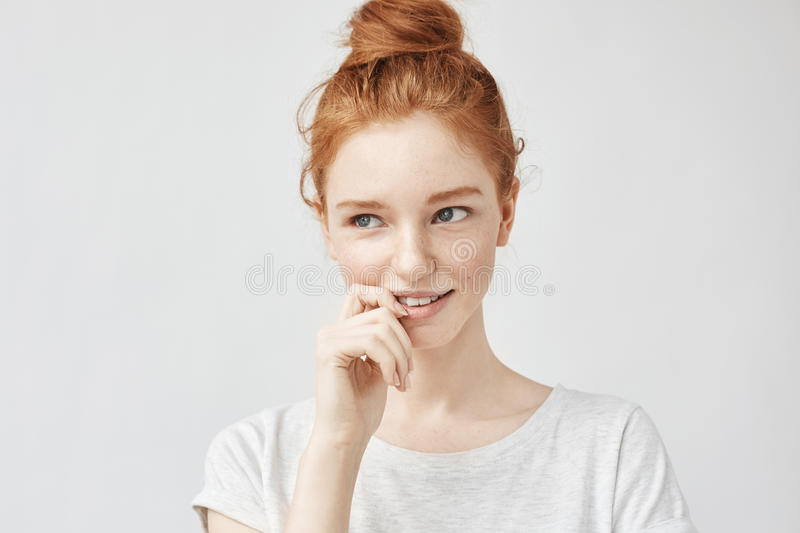 Portrait of shy beautiful girl with foxy hair and freckles smiling. Copy space. Isolated on white background royalty free stock photography