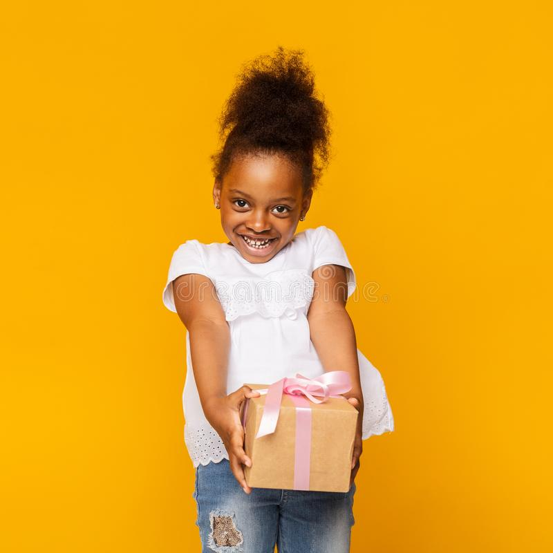 Portrait of shy little african girl with gift box stock photo