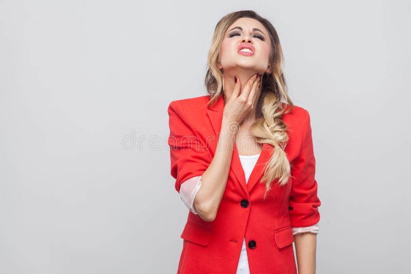 Portrait of sick beautiful business lady with hairstyle and makeup in red fancy blazer standing, touching her neck and feeling. Throat pain. indoor studio shot royalty free stock images