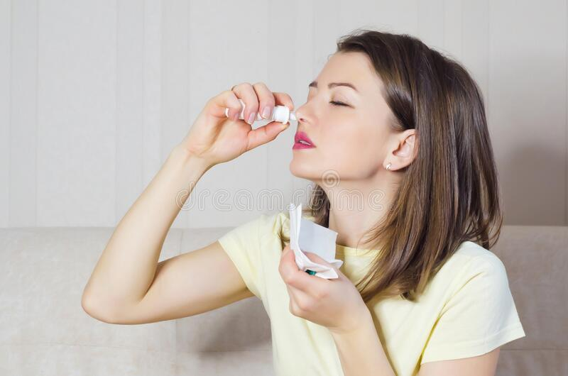 Portrait of sick girl with runny nose, rhinitis, allergies, colds. woman holds medical spray in hand. Soft focus stock photography