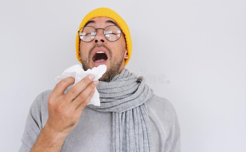 Portrait of sick handsome man wearing grey sweater, yellow hat and spectacles, blowing nose and sneeze into tissue. Male have flu. Virus or allergy respiratory stock photos