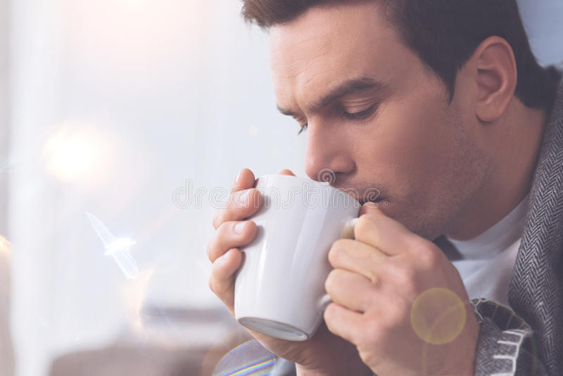 Portrait of sick male person keeping cup near lips. Stay at home. Frustrated man wrinkling his forehead looking downwards into cup while warming himself with tea royalty free stock photography