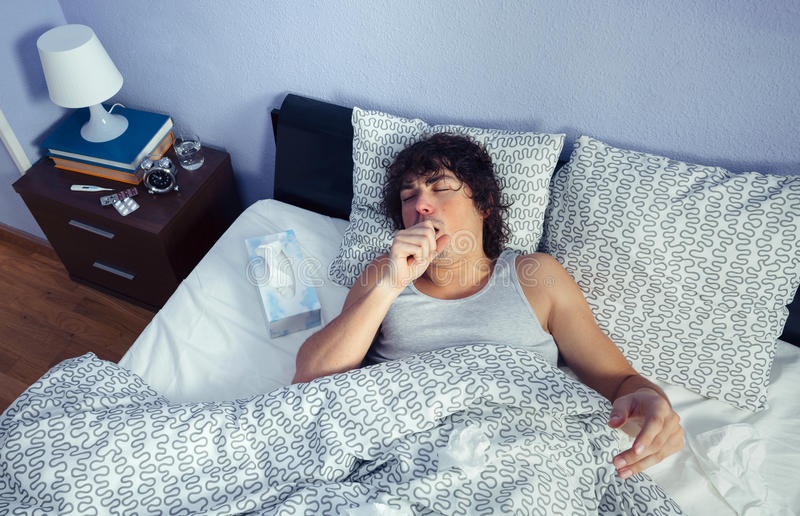 Portrait of sick man coughing lying on bed stock photo
