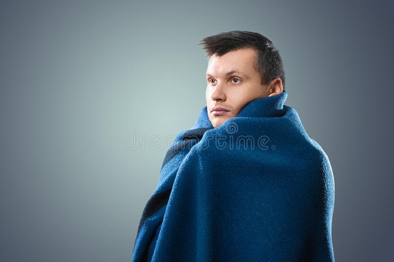 Portrait of a sick man with flu, allergy, germs, cold. Wrapped In a blanket against a light background. Portrait of a sick man with flu, allergy germs cold stock image