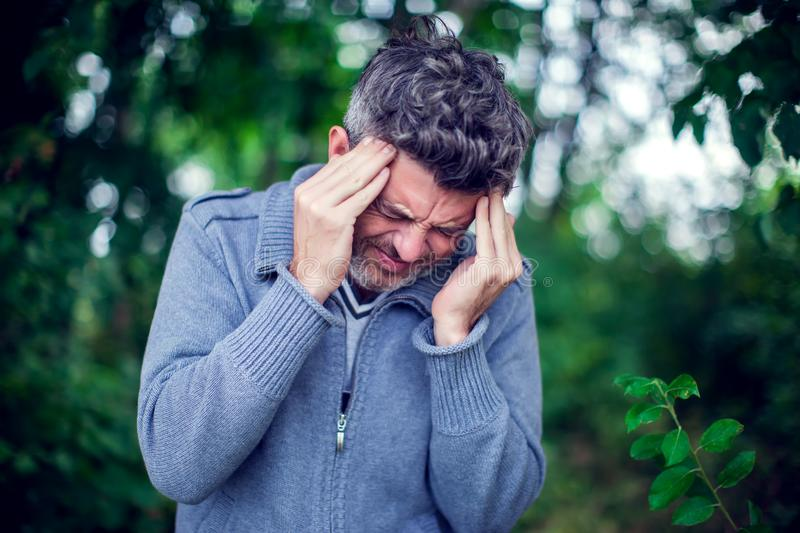 Portrait of a sick man having a migraine outdoor. Healthcare, me royalty free stock photo