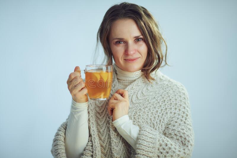 Sick modern 40 years old housewife showing cup of tea stock photo