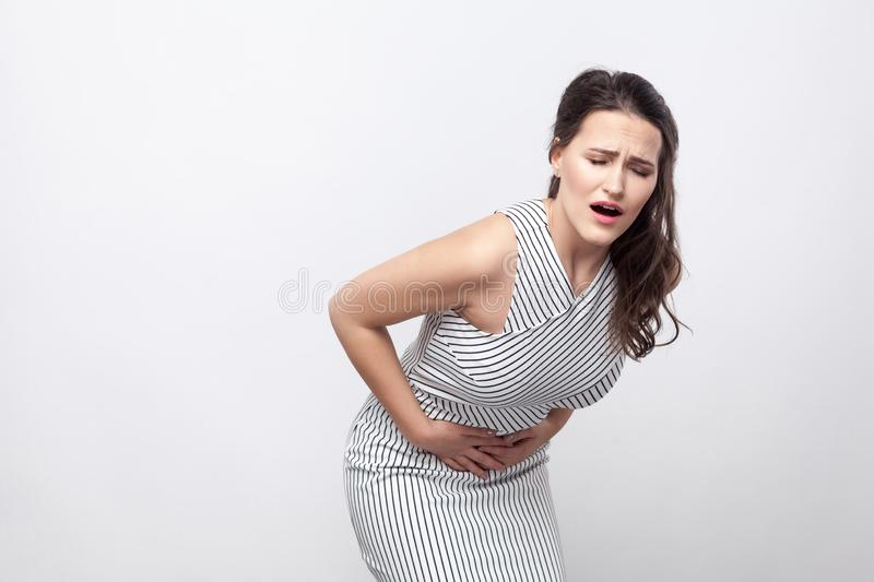 Portrait of sick unhappy young brunette woman with makeup and striped dress standing with stomach pain and holding her painful stock image