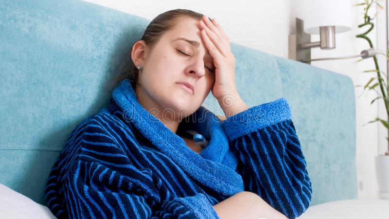 Closeup portrait of sick woman caught cold lying in bed and suffering from headache royalty free stock photography