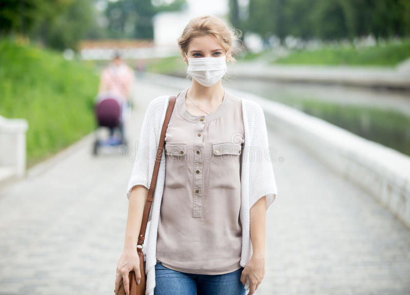 Portrait of sick woman wearing protective mask against infective diseases. Portrait of beautiful woman walking on the street wearing protective mask as royalty free stock images